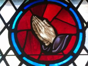Stained glass prayer hands.
