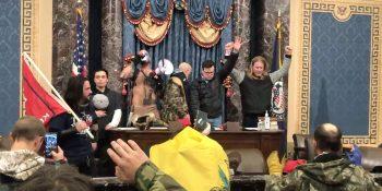 Insurrectionists pray in Senate chamber.